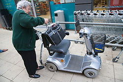 Older woman loading her shopping bag onto electronic mobility scooter,