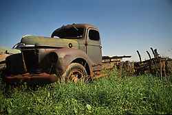 abandoned decaying rusting truck in country field.