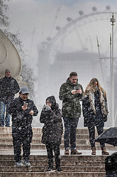 © Licensed to London News Pictures. 26/02/2018. London, UK. Tourists brave heavy snow as they stand on Queen Victoria Memorial at Buckingham Palace as a cold front sweeps in from the east - with heavy snow expected later in parts of the UK. Photo credit: Peter Macdiarmid/LNP