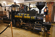 1879 locomotive of the Homestake Mining Company, in the Adams Museum in Deadwood, Lawrence County, South Dakota, USA. The Historic Adams House was built in 1892 by Deadwood pioneers Harris and Anna Franklin. After the discovery of large placer gold deposits in Deadwood Gulch in 1875, thousands of gold-seekers flocked to the new town of Deadwood from 1876 to 1879, leading to the Black Hills Gold Rush, despite the land being owned by the Sioux. At its height, the city had a population of 25,000, and attracted larger-than-life Old West figures including Wyatt Earp, Calamity Jane, and Wild Bill Hickok (who was killed there). The entire city is now designated as a National Historic Landmark District, for its well-preserved Gold Rush-era architecture.