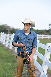 cowboy with bridle walking on a ranch