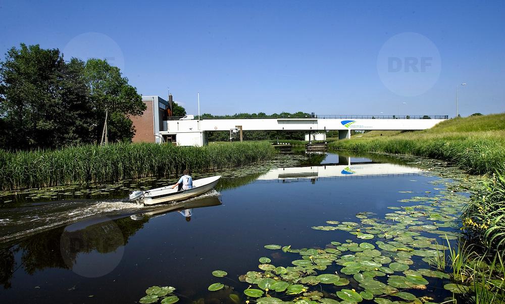 Nederland Moordrecht 24 mei 2007 20070524..Jongen vaart met bootje door watergang met op de achtergrond het gemaal ..Serie tbv Schieland en de Krimpenerwaard, deze zorgt als waterschap voor droge voeten en schoon water in een bepaald gebied. Het beheersgebied van Schieland en de Krimpenerwaard strekt zich uit tussen Rotterdam, Schoonhoven en Zoetermeer. Binnen dit gebied zorgt Schieland en de Krimpenerwaard voor de kwaliteit van het oppervlaktewater, het waterpeil en de waterkeringen. Daarnaast beheert Schieland en de Krimpenerwaard een aantal wegen in de Krimpenerwaard...Foto David Rozing