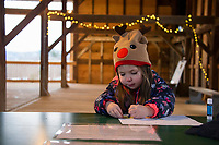 Sophie Dutchka works on her craft project showing the phases of the Moon cycle during Prescott Farm Environmental Center's Winter Solstice celebration on Saturday afternoon.  (Karen Bobotas/for the Laconia Daily Sun)