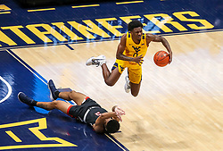 Jan 25, 2021; Morgantown, West Virginia, USA; West Virginia Mountaineers guard Kedrian Johnson (0) trips over Texas Tech Red Raiders guard Micah Peavy (5) during the second half at WVU Coliseum. Mandatory Credit: Ben Queen-USA TODAY Sports