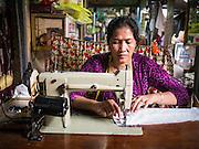 02 FEBRUARY 2013 - PHNOM PENH, CAMBODIA:  A seamstress works in a market in Phnom Penh, Cambodia.      PHOTO BY JACK KURTZ