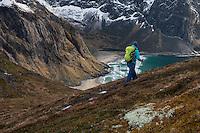 Female hiker with view over Kvalvika beach on trail to Ryten, Moskenesøy, Lofoten Islands, Norway