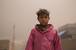 Licensed to London News Pictures. 08/11/2016. Qayyarah, Iraq. A young oil covered Iraqi boy is seen on a smokey street in Qayyarah, Iraq. Oil wells in and around the town of Qayyarah, Iraq, we set alight in July 2016 by Islamic State extremists as the Iraqi military began an offensive to liberated the town.<br /> <br /> For two months the residents of the town have lived under an almost constant smoke cloud, the only respite coming when the wind changes. Those in the town, despite having been freed from ISIS occupation, now live with little power, a water supply tainted with oil that only comes on periodically and an oppressive cloud of smoke that coats everything with thick soot. Many complain of respiratory problems, but the long term health implications for the men, women and children living in the town have yet to be seen. Photo credit: Matt Cetti-Roberts/LNP