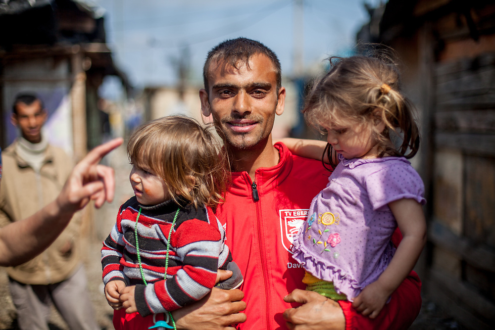 """A young father with his two children at the Roma settlement located at """"Budulovska Street"""" in Moldava nad Bodvou about 30 km from Kosice. From about 800 inhabitants of the segregated settlement 'Budulovska Street' (2014) are roughly 392 children up to the age of 16 years."""