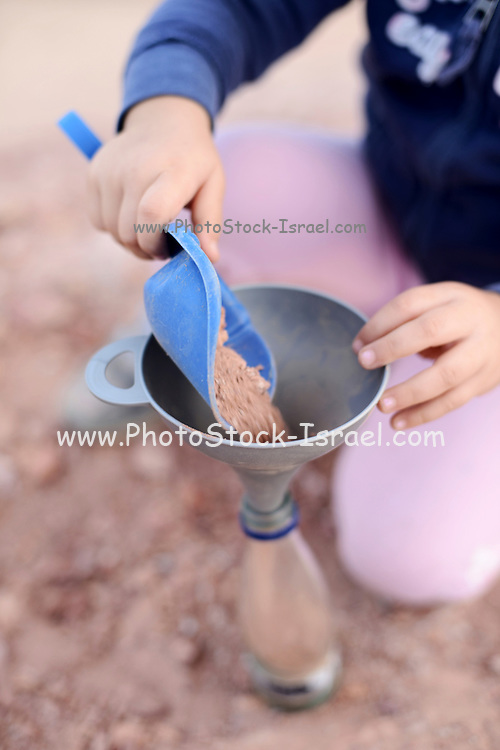 Young girl colects coloured sand at HaMakhtesh HaGadol (The Big Crater) is a makhtesh, a geological erosional landform of Israel's Negev desert. It measures 5 x 10 km.