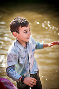 A child plays before being baptized in the river crossing of the Vado del Quema