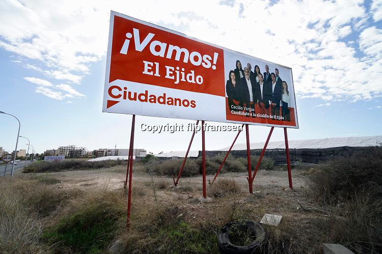 Spanje, El Ejido, 6-11-2019 Straatbeeld uit El Ejido . Een verkiezingsbord van de politikeke partij Cuidadamos . In dit deel van Andalucie worden veel groente en fruit verbouwd die hun weg vinden via de export naar o.a. Nederland . Het wordt de zee van plastic genoemd. Komende week zijn er algemene verkiezingen in Spanje en de populistische partij Vox heeft hier een grote aanhang. In de kassen werken voornamelijk migranten uit Afrika, en arbeidsmigranten uit Oost-Europa die een laag loon uitbetaald krijgen, tussen de 30 en 40 euro per 8 urige dag, werkdag, afhankelijk van de werkgever. Er wordt door de kaseigenaren en transportbedrijven goed verdiend maar de boeren vinden dat ze teveel negatieve aandacht krijgen in de media in noord-europa. Foto: Flip Franssen