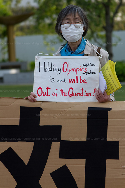 A woman holds a sign saying The Olympics is out of the Question as people take part in a demonstration against the delayed 2020 Tokyo Olympics Games in Gaiemmae, Tokyo, Japan. Sunday May 9th 2021. About 100 people took part in a demo outside the Japanese Olympic Committee museum and marched around the new Olympic Stadium to protest holding the event while the  the COVID-19 pandemic is still seriously affecting Japan.