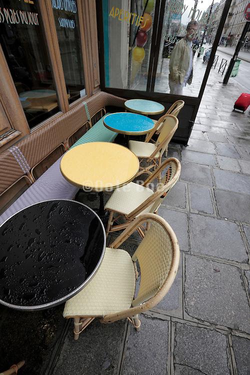 wet empty bistro tables on a Paris sidewalk