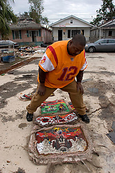 10 December, 05.  New Orleans, Louisiana.  Post Katrina aftermath.<br /> A lavish Mardi Gras Indian costume is laid out in the front yard of a devastated home in Gentilly, New Orleans.<br /> Photo; ©Charlie Varley/varleypix.com