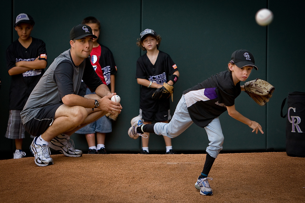 Colorado Rockies pitcher JEFF FRANCIS assists 10 year-old LIAM MURRAY with his throws during the Back To The Basics Clinic held by the Rockies for their young fan club at Coors Field.