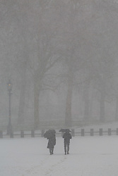 Two people make their way across Horseguards Parade as a sudden snow flurry hits Westminster. Westminster, London, February 27 2018.