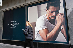 Glasgow, Scotland, UK. 26 October 2020. View of Glasgow city centre on weekday during circuit breaker lockdown with bars and restaurants closed. Pictured; Woman walks past billboard of David Gandy on Marks & Spencer store . Iain Masterton/Alamy Live News