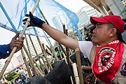 Apr. 30 - BANGKOK, THAILAND: A Red Shirt jams bamboo stakes into the new barricade they built in Sala Daeng intersection in Bangkok. The Red Shirts moved one of their barricades in the Sala Daeng Intersection in Bangkok Friday In one of the first positive moves to take place since the Red Shirts occupied central Bangkok in early April. The barricade was moved far enough back to open one lane of traffic on  Ratchadamri Street to allow ambulance access to King Chulalongkorn Memorial Hospital, a large hospital at the intersection. Many of the patients in the hospital have been moved to other hospitals because a group of Red Shirts entered the hospital Thursday looking for Thai security personnel, who were not in the hospital. The stand off between the Red Shirts and the government enters its third month in May. The Red Shirts continue to call for Thai Prime Minister Abhisit Vejjajiva to step down and dissolve parliament and demand the return of ousted Prime Minister Thaksin Shinawatra.   PHOTO BY JACK KURTZ
