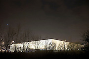 The form of a giant generic warehouse glows from ambient light at the DIRFT warehouse logistics park in Daventry, Northamptonshire England. Bare trees without foliage are seen in the foreground on this cold winter night. We see the building low in the picture and the sky graduates from light into near darkness. This 365 acre site off Junction 18 of the M1 motorway is a hub for road, rail and service infrastructure, some 2.3m sq.ft. of distribution and manufacturing floorspace had been constructed by 2004 and occupiers including Tesco?s, Tibbett & Britten plc, Ingram Micro, Royal Mail, the W.H. Malcolm Group, Eddie Stobart Ltd, Wincanton and Exel, have been attracted to this unique logistics location.
