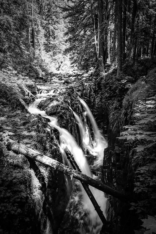 """Sol Duc Falls (pronounced """"Soul Duck"""") is one of many hundreds of waterfalls found in the Olympic Peninsula's temperate rain forest in Washington State, and also one of the most beautiful. Somewhat isolated, and off the regular beaten path of most day-hikers (except for locals) and tourists this raging waterfall can be visited year round. The Sol Duc River gets its name from the Quileute (also spelled Quillayute) word roughly translated as """"magic waters."""""""