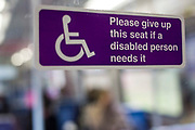 A disability sign on a Greater Anglia train requesting customers give up a seat for disabled person. UK.