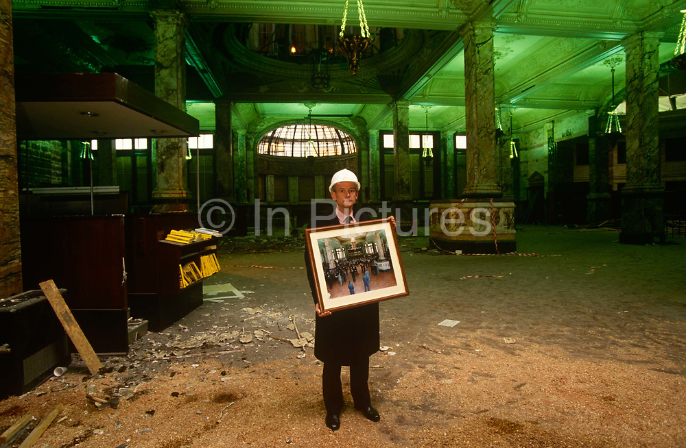A portrait of an executive from the Baltic Exchange holding a framed photo of what the trading institution before it was wrecked by the IRA terrorist bomb nearby in St Mary Axe in the City of London. On 10 April 1992 at 9:20 pm, the façade of the Exchange's offices at 30 St Mary Axe was partially demolished and the rest of the building was extensively damaged in the Provisional Irish Republican Army bomb attack. The one-ton bomb was contained in a large white truck and consisted killed three people. Too heavily damaged, a full restoration of the premises was ruled out and the hall was completely razed in 1998. The Baltic Exchange is the world's only independent source of maritime market information for the trading and settlement of physical and derivative contracts.