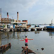 Boys fishing in the waters of the Havana bay, at Regla area.