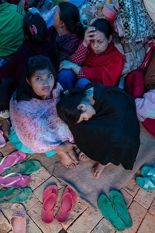 Women left homeless when their homes were destroyed by the 2015 Nepal earthquake shelter in a temporary camp.