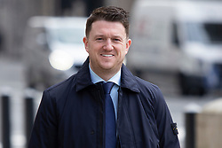 """© Licensed to London News Pictures. 22/03/2021. London, UK. Tommy Robinson arrives at the Royal Courts of Justice for a preliminary hearing in a libel case brought against him by Jamal Hijazi. The EDL founder commented on a video of Jamal Hijazi being attacked in a school and claimed that """"he was not innocent and he violently attacks young English girls in his school"""".   Photo credit: George Cracknell Wright/LNP"""