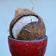 Broken coconut in a red egg-like holder