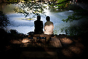 TOKYO, JAPAN, 28 APRIL - kichijoji -A couple wearing black and white cloth are sitting in front of a pond - April 2012
