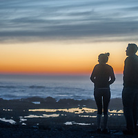 A couple admires the sunset at Fitzgerald Marine Reserve in Moss Beach, California.