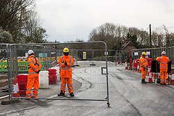 Harefield, UK. 6th April, 2021. HS2 security guards monitor a gate at the junction of Dews Lane and Harvil Road where works for the HS2 high-speed rail link are taking place. Thousands of trees have already been felled in the Colne Valley where HS2 works will include the construction of a Colne Valley Viaduct across lakes and waterways and electricity pylon relocation.