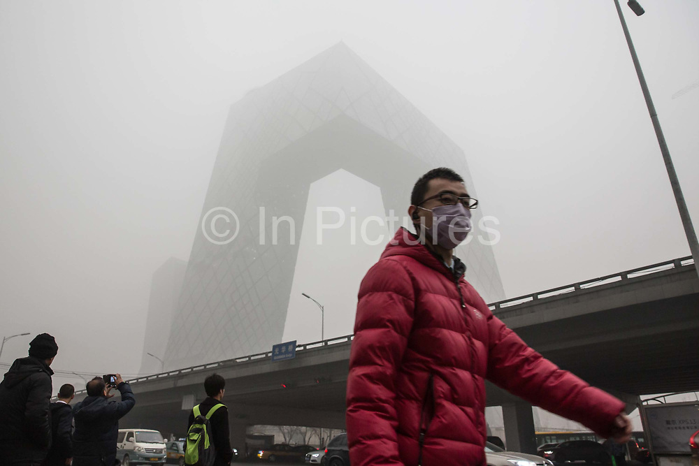A pedestrian wearing a face mask walks past the China Central Television CCTV headquarters building shrouded in haze in Beijing, China, on Monday, Nov. 30, 2015.  China has made a concerted effort to cut down pollution, especially in the nation capital, however there are still heavily polluted days especially in the winter months.