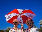 """11 NOVEMBER 2013 - PHOENIX, AZ: Women under a parasol watch the Phoenix Veterans Day Parade. The Phoenix Veterans Day Parade is one of the largest in the United States. Thousands of people line the 3.5 mile parade route and more than 85 units participate in the parade. The theme of this year's parade is """"saluting America's veterans.""""     PHOTO BY JACK KURTZ"""