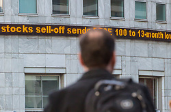 A worker passes the ticker at Canary Wharf telling him FTSE 100 stocks have plummeted to a 13 month low as European markets follow US and Asian markets lower on Tuesday as investors continued to dump shares. London, February 06 2018.