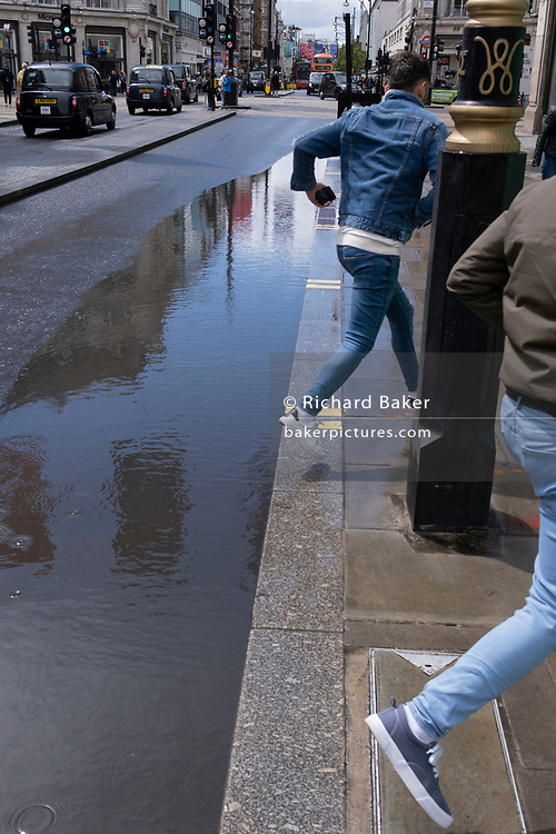 Young men reach the pavement after jumping a puddle left by seasonal Spring rainfall on Oxford Street, on 24th May 2021, in London, England.