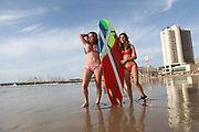 Two young girls enjoying a summer day on the beach with a surfboard Photographed in Tel Aviv, Israel