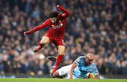 Manchester City's Vincent Kompany (right) tackles Liverpool's Mohamed Salah, resulting in a yellow card, during the Premier League match at the Etihad Stadium, Manchester.