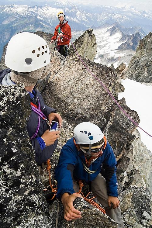 Climbers gather on the narrow summit of Dorado Needle, a rocky spire on the Eldorado Icecap in North Cascades National Park, Washington.