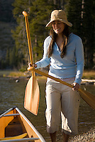 A young woman prepares for canoeing on String Lake in Grand Teton National Park, Jackson Hole, Wyoming.
