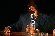 A businessman of Asian descent has stopped at a bar in the City of London and is seated by the window in a bar.