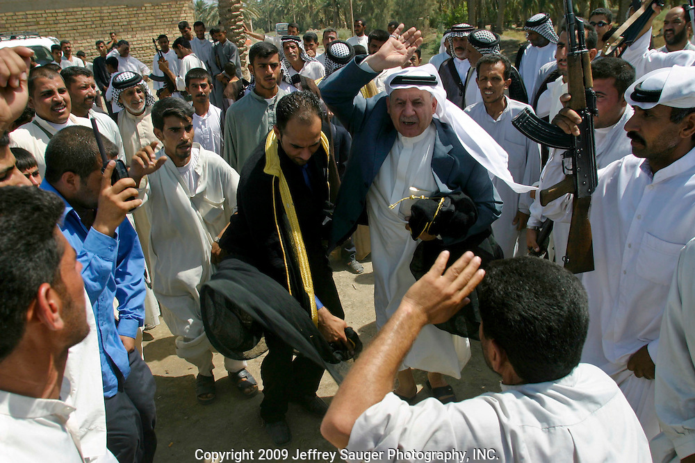 Emad Al-kasid, left in gold and black, and his father Malik Al-kasid, in gray suit coat, participate in Hawaies, a traditional tribal Arabic dance, at the Al-kasid family's Istikbal, or homecoming, in their home village Suq ash Shuyukh about 20 miles southeast of Nasiriyah, Iraq, Tuesday, July 29, 2003. ..When Malik Al-kasid's caravan approached, guns were fired to announce his family's arrival. The welcming party then, returns fire to welcome him. The two parties move toward each other dancing and shooting until they join in the middle where the Hawaies occurs. ..The Al-kasid family fled Iraq after the Gulf War and their part in the uprising against Saddam Hussein in 1991, spent 3 years in Rafa, Saudi Arabia and finally settled in Dearborn, MI. The family hasn't been home to Iraq in 13 years.