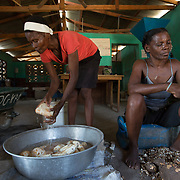 """CAPTION: Before milling, the peeled cassava has to be washed thoroughly. 40% of the beneficiaries of this project are women. According to Marc-Lucien Jerome, Founder and Trainer of OGKPS, """"Women are our mothers and daughters, we have to give back to them; they have played a big role in our independence."""" ORGANIZATION: Organizasyon Gwoupman Kominotè Pawas Sakretè (OGKPS). LOCATION: #88 Laviolette (Monte Pa Desann), Cap-Haïtien, Haiti. INDIVIDUAL(S) PHOTOGRAPHED: Soicina Bien-Aimé (left) and Isabelle Saintilma (right)."""