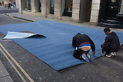 A team of Asian men measure and cut a roll of industrial carpet in a side street and destined for a nearby shop in London's New Bond Street.