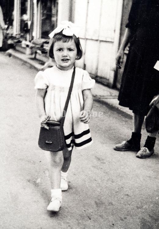 little girl walking in the street France ca 1950s