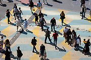 A population of diverse and ethnic shoppers and other pedestrians cross the road in Stratford, on 11th August 2021, in London, England.