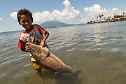Siti Rofi'ah's step grandson Mohamad, 6, helps bring fish ashore in Lewoleba, Nubatukan subdistrict, Lembata district, East Nusa Tenggara province, Indonesia.