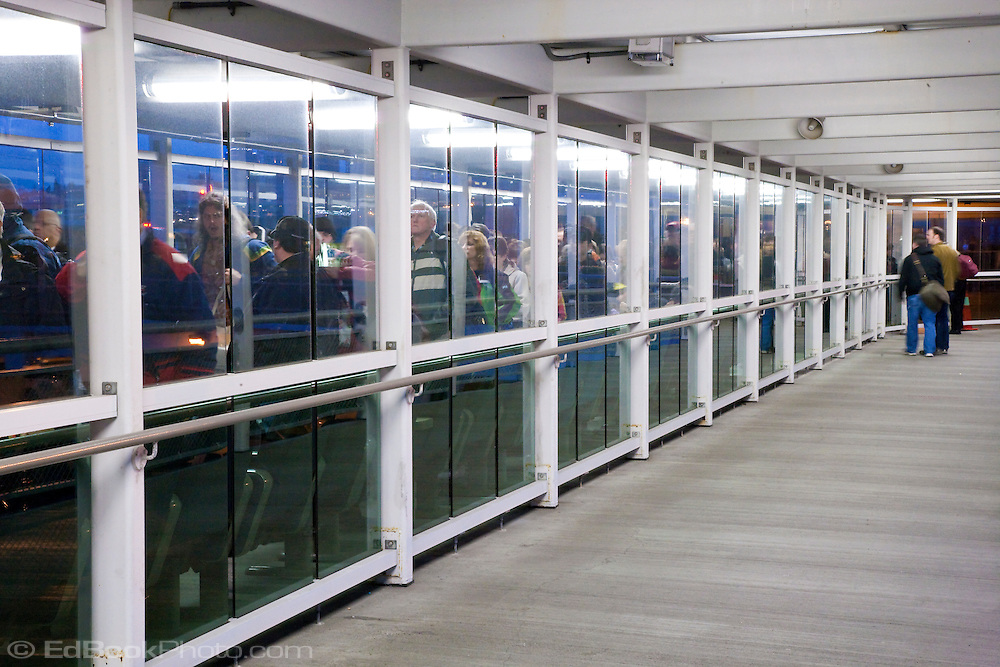 a queue of ferry passengers move along the gangway to load a Washington State Ferry at Seattle, Washington, USA