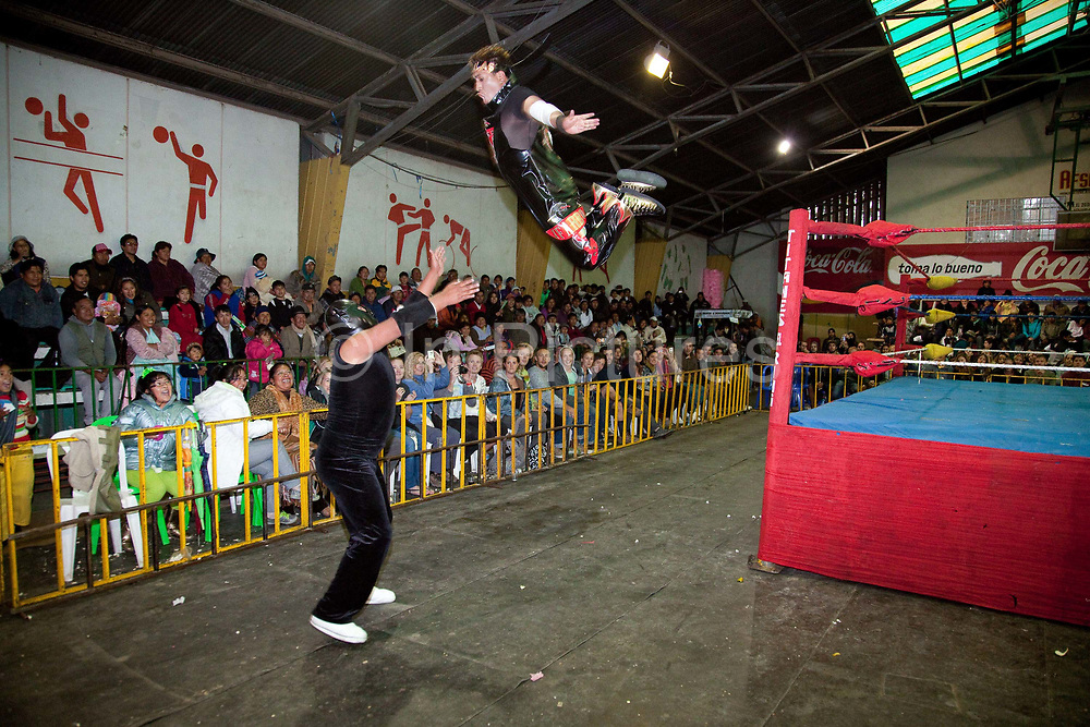 Male wrestler jumping out of ring onto his opponent. Lucha Libre wrestling origniated in Mexico, but is popular in other latin Amercian countries, including in La Paz / El Alto, Bolivia. Male and female fighters participate in the theatrical staged fights to an adoring crowd of locals and foreigners alike.
